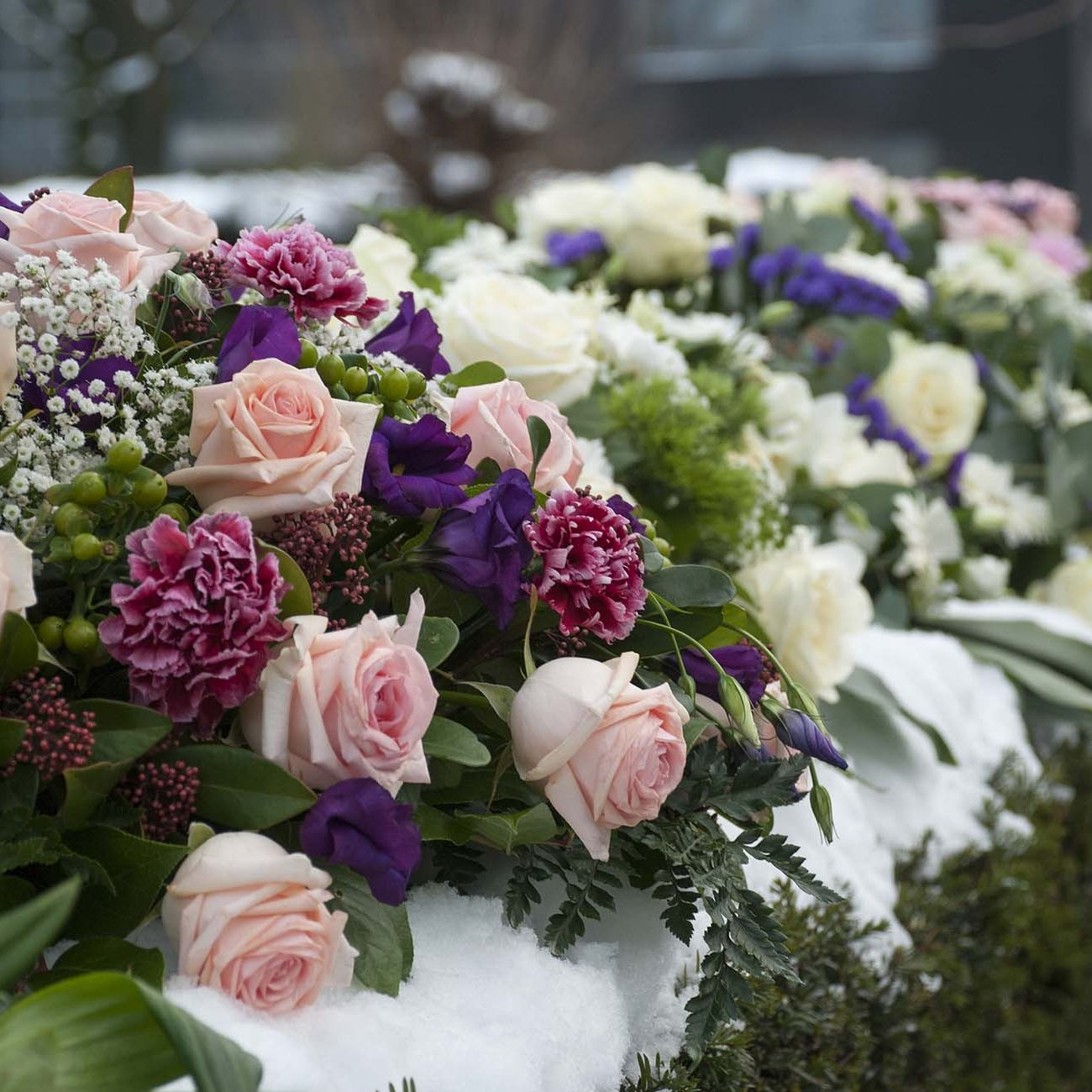 Several funeral flowers arrangements in the snow on a hedge at the cemetery